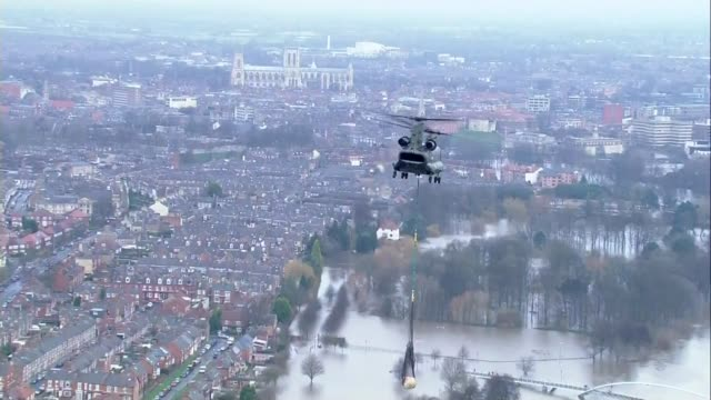 vídeos de stock e filmes b-roll de environment agency bosses appear before commons select committee / t28121501 yorkshire york chinook helicopter flies over flooded area of york york... - baixar