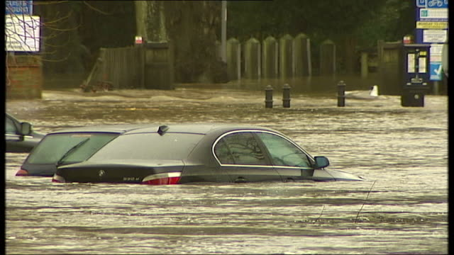 Guildford general views ENGLAND Surrey Guildford EXT Parlially submerged road sign 'Riverside Walk' / fastflowing flood water / man taking photograph...