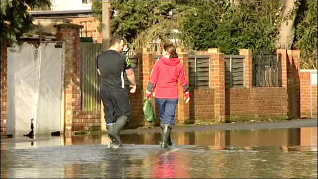 GVs Thames Valley Surrey Staines upon Thames Flooded street and houses / clouds in sky PAN flooded streets and houses / sand bags piled up outside /...
