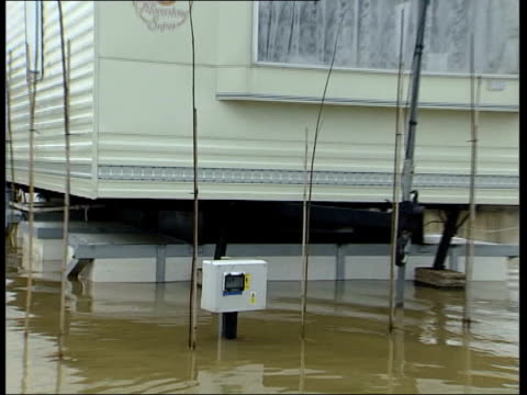 yalding man pulling boat through flooded street ms couple towards through flood water in waders gv flooded mobile home park with mobile homes raised... - amfibiefordon bildbanksvideor och videomaterial från bakom kulisserna