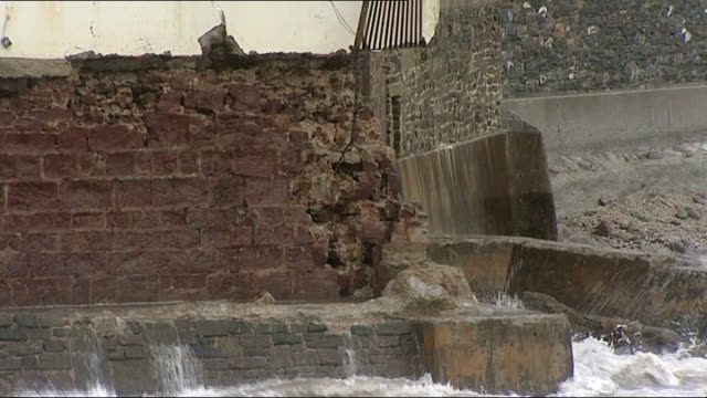 cornwall kingsand ext waves crashing near damaged clock tower / damaged railings / debris on streets / firefighters along / damaged street / damaged... - kingsand video stock e b–roll