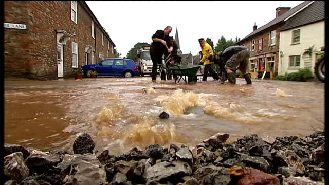 Flooding in England and Wales / Continued drought measures ENGLAND Somerset East Harptree EXT GVs Resident Brian Sills sweeping away floodwater from...