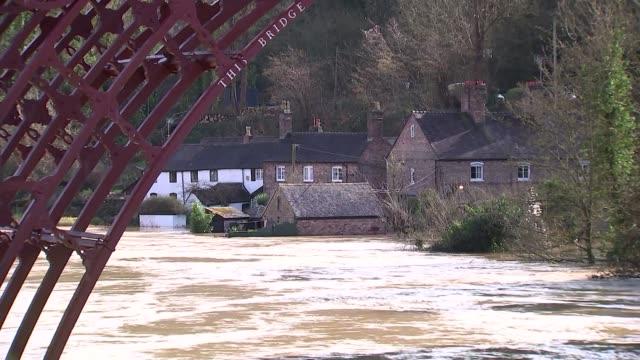 flooding in ironbridge; england: shropshire: ironbridge: ext various shots of flood defences along river / various shots of bridge and flood defences... - ironbridge shropshire stock videos & royalty-free footage