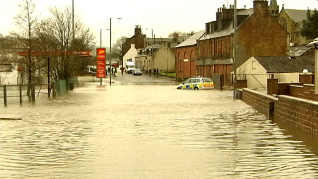 Ayrshire New Cumnock EXT Flooded town centre street woth police car partially submerged in floodwater Row of semidetached houses with flooded street...