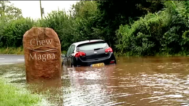 flooding in somerset and herefordshire / strong winds hit britain; england: somerset: chew magna: ext man carrying his daughter through floodwater... - herefordshire bildbanksvideor och videomaterial från bakom kulisserna