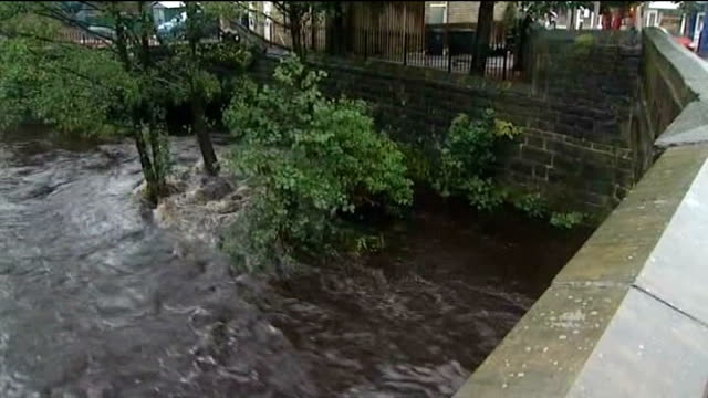 flooding in somerset and herefordshire / strong winds hit britain; yorkshire: hebden bridge: high angle shot of river calder flowing at high level to... - herefordshire bildbanksvideor och videomaterial från bakom kulisserna