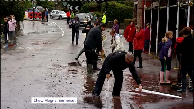 flooding in somerset and herefordshire / strong winds hit britain england somerset chew magna ext various of people in flooded street poking drains... - toccare con un dito video stock e b–roll