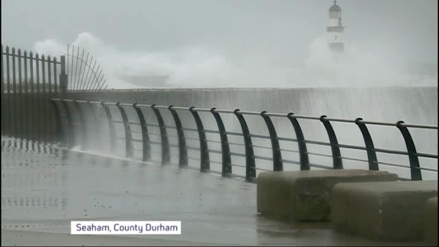flooding in somerset and herefordshire / strong winds hit britain; england: county durham: seaham: ext waves crashing over promenade fencing man... - herefordshire bildbanksvideor och videomaterial från bakom kulisserna