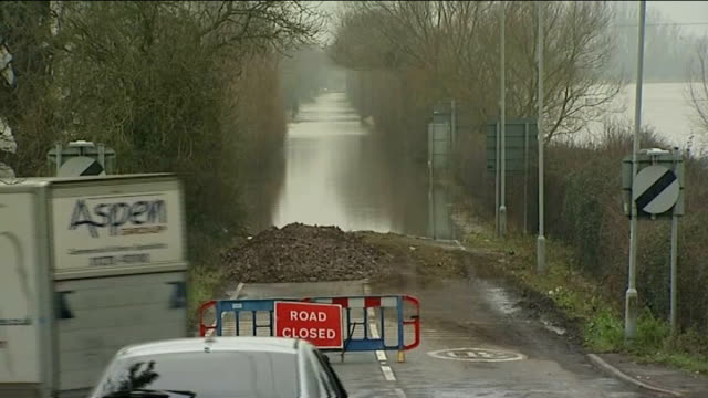 Pumps arrive ENGLAND Somerset EXT Sign for the River Parrett and temporary flood defences lining the rover bank / Road Closed sign at top of flooded...