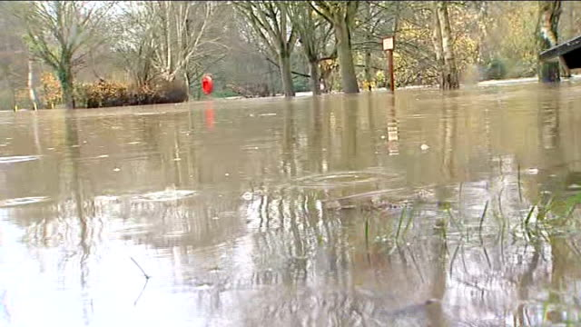 Keynsham ENGLAND Somerset Keynsham EXT Car standing in flooded area / Sign Danger Deep Water standing in floodwater of swollen river / picnic benches...