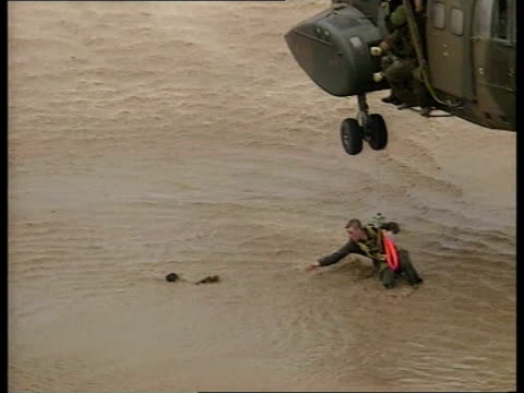 vídeos de stock e filmes b-roll de flooding mozambique / natural disasters flooding itn mozambique ext air to air rescue helicopter hovering over tree in which family are sheltering... - moçambique