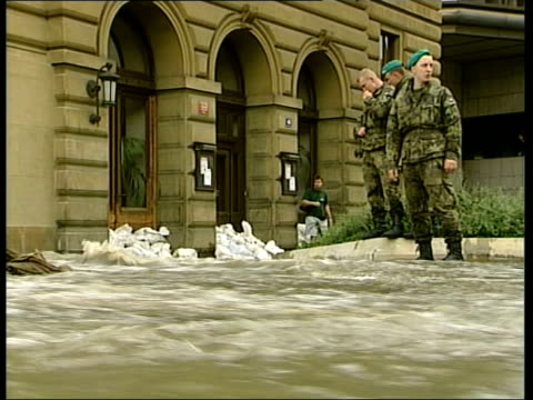 prague under threat; itn i/c iron railings of bridge as flooded river water coming over edge legs of local residents as piling sandbags along edge of... - 緊急用具点の映像素材/bロール