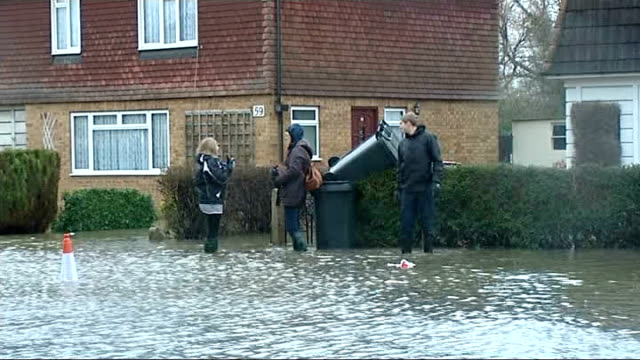 Staines ENGLAND Surrey Staines EXT Car stranded in floodwater / GVs flooded streets / broken sign for flood evacuation route / people emptying...