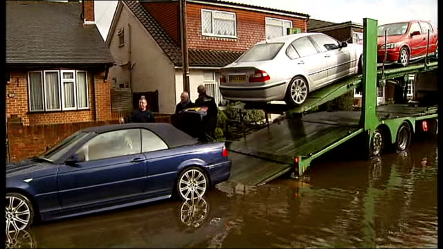 Thames flood victims may have 6 month wait to get back into their homes ENGLAND Surrey Egham EXT Pump and pipe across road where flood water is...