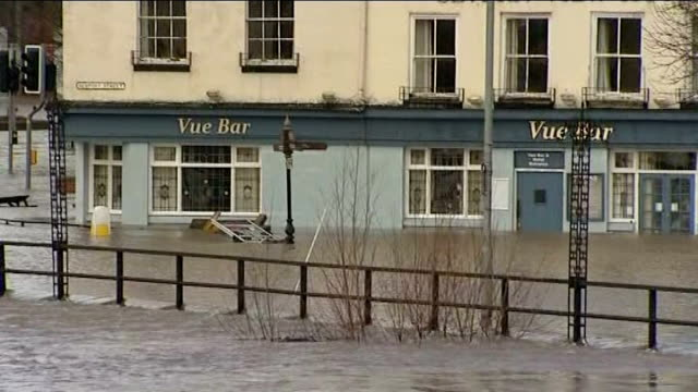 Worcester Floodwater and buildings / debris in water / Avis petrol station / flooded Vue bar / more of bridge clogged with debris / man cycling...