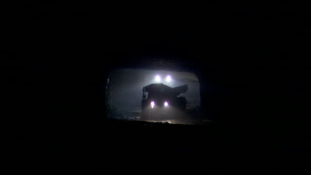 floodlights illuminate a construction vehicle as it backs in a tunnel. - construction vehicle stock videos & royalty-free footage
