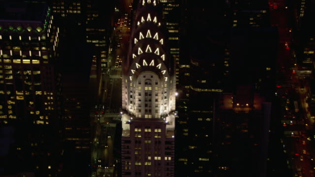 floodlights illuminate the spire of the chrysler building. - chrysler building stock videos & royalty-free footage