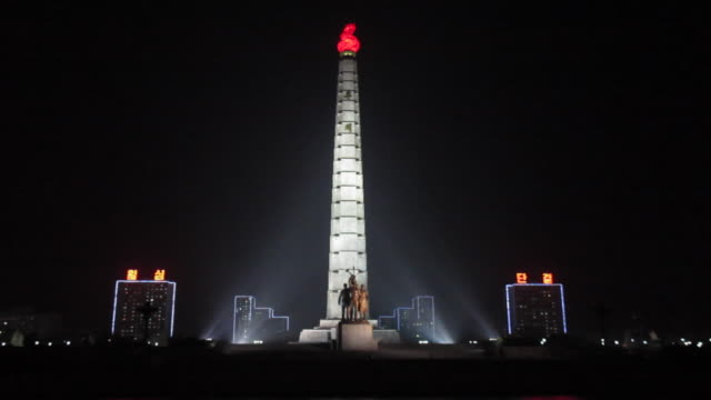 Floodlights illuminate the Tower of Juche in Kim ll Sung Square.