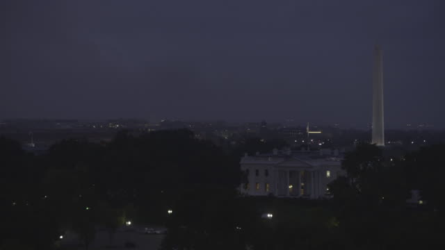 Floodlights illuminate the Washington Monument as it towers above the National Mall behind the White House.