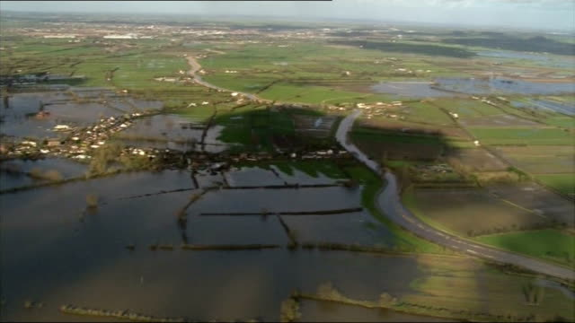 air views of somerset levels burrowbridge water being pumped into overflowing river / wide shot flooded somerset levels / swans on the water south... - somerset levels stock videos and b-roll footage