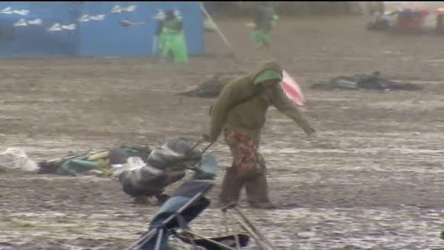 floods cause chaos in britain; somerset: glastonbury: 2007 glastonbury festival: festival-goer pulling trolley along thru rain and mud festival-goer... - festival goer stock videos & royalty-free footage