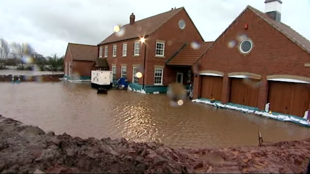 flood barrier built around house marooned in flood water england somerset levels muchelney / moorland ext shot along past flooded houses to house on... - somerset england stock-videos und b-roll-filmmaterial