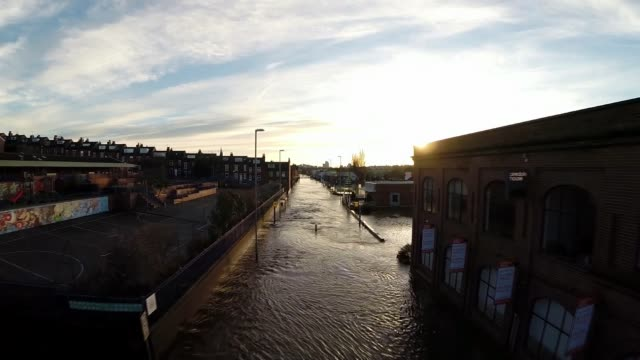 leeds residents blame government cuts for flooding; lib / england: yorkshire: leeds: ext air view / aerial drone footage of flooded kirkstall road - leeds stock videos & royalty-free footage