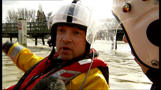 River Thames floods between Datchet and Shepperton Reporter shaking hands with RNLI crew member then climbing into inflatable lifeboat Wheels of...