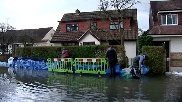 river thames floods between datchet and shepperton; sandbags across flooded driveway people putting barrier in front of house sandbags being put at... - 防水シート点の映像素材/bロール