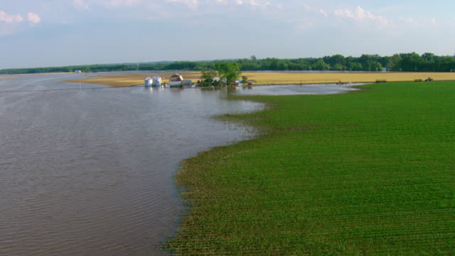 floodwater surrounds a barn, silos, and farmhouse. - farmhouse stock videos & royalty-free footage