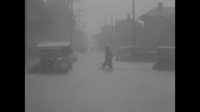 floodwaters and partially submerged cars with a man wading past / title who said 'it ain't goin' rain no more' / cars driving on wet roads and little... - washtub stock videos and b-roll footage