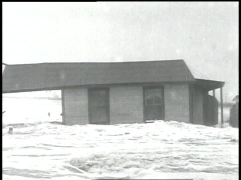 stockvideo's en b-roll-footage met floodwaters destroy buildings as hurricane sweeps into new united kingdom / united states - 1938
