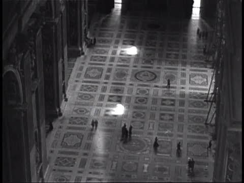floor below dome w/ people walking. latin inscription on wall 'tu es petrus...' [thou art peter] '... super hanc petram' [upon this rock] - 使徒点の映像素材/bロール
