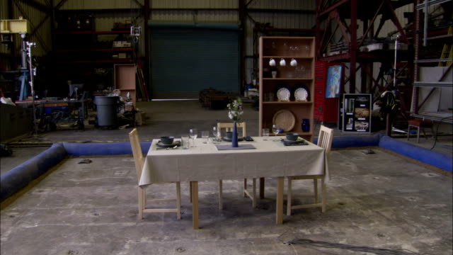 A floor trembles shaking place settings on a table and crockery in a cabinet. Available in HD.
