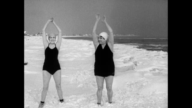 Flora Marshant and her friend Mrs Favier wearing bathing suits smile into camera before commencing warm up exercises on beach / women run through the...