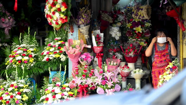 floral shopkeeper putting on a surgical face mask while standing in front of her shop - bangkok stock-videos und b-roll-filmmaterial