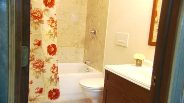 a floral shower curtain decorates a bathroom pod inside a factory warehouse. - shower curtain stock videos and b-roll footage
