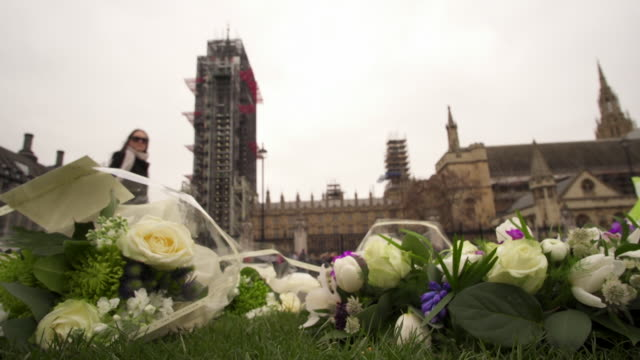 floral tributes outside the houses of parliament on the one year anniversary of the westminster terror attack - シティ・オブ・ウェストミンスター点の映像素材/bロール
