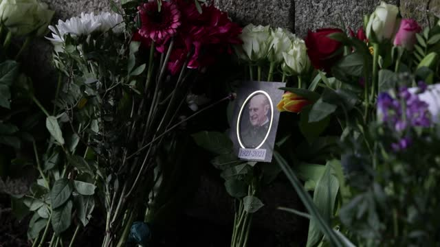 floral tributes to prince philip, duke of edinburgh left outside windsor castle on april 14, 2021 in windsor, united kingdom. the queen announced the... - ウィンザー城点の映像素材/bロール