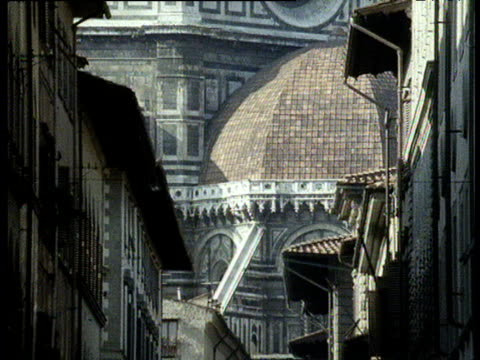 florence dumo from vista of alleyway tilt up to huge red dome and spire atop - kuppeldach oder kuppel stock-videos und b-roll-filmmaterial
