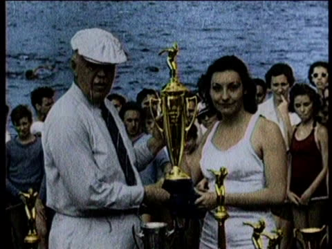 vídeos de stock e filmes b-roll de florence holds a golden trophy in the crowd / in a maroon suit and hat holding her luggage she smiles and waves to line of cameramen / she greets a... - touca de natação
