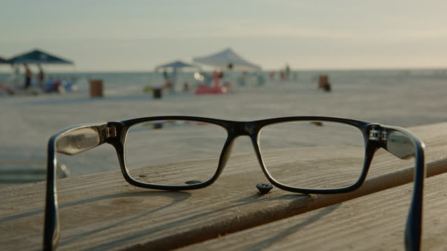 Florida beach eye glasses sunset people bench sand summer