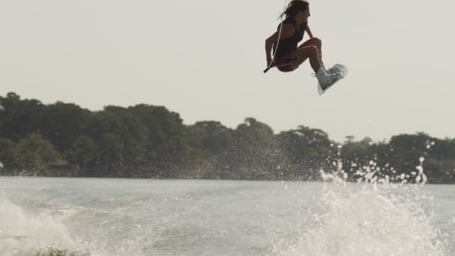 usa, florida, orlando, maitland lake, woman jumping on wakeboard - wakeboarding stock videos and b-roll footage
