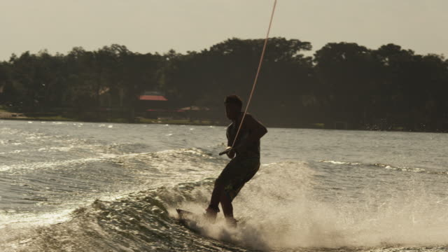 usa, florida, orlando, maitland lake. young man on wakeboard - wakeboarding stock videos and b-roll footage