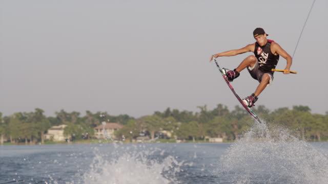 usa, florida, orlando, maitland lake. young man on wakeboard - ウェイクボーディング点の映像素材/bロール