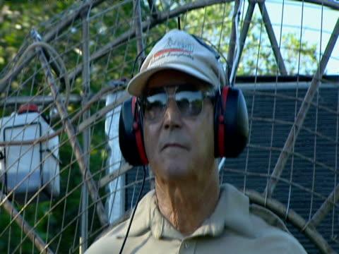 florida park-ranger wearing sunglasses and ear-guards piloting fan-boat in everglades - 公園保安官点の映像素材/bロール