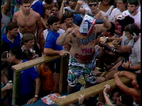 Young Man Doing a Belly Flop into a Pool in Front of a Crowd