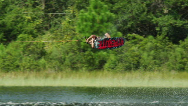 usa, florida, young man doing trick on wakeboard - wakeboarding stock videos and b-roll footage