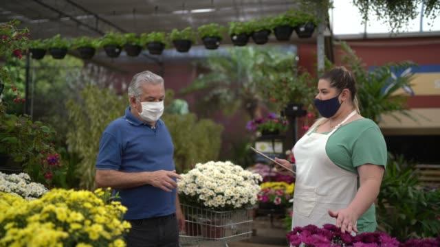 フェイスマスクを着用したガーデンショップで購入する花屋と顧客 - フローリスト点の映像素材/bロール