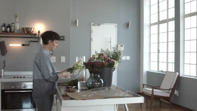 florist arranging fresh flower in vase at kitchen island - arbeitsplatte stock-videos und b-roll-filmmaterial